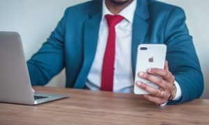 Man in blue suit looks at iPhone